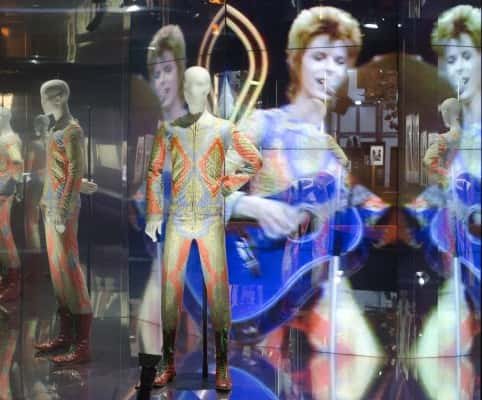 David Bowie appears on a giant screen with various costumes he performed in, as part of a retrospective David Bowie exhibition, entitled David Bowie Is, aat Paris Philharmonic Museum, France. Friday, Feb. 27, 2013, that features 300 objects including handwritten lyrics, original costumes, fashion, photography, film, music videos, set designs and Bowie's own instruments.(AP Photo/Jacques Brinon)