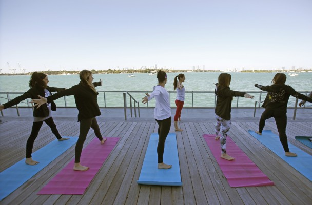In this Jan. 24, 2016, photo, Paula Walker, background center, an instructor with Green Monkey Yoga, leads a yoga class at the Mondrian South Beach Hotel in Miami Beach, Fla. The hotel world is moving beyond basement gyms and ho-hum spa menus to accommodate guests' growing requests to stay healthy while on the road. The number of hotels with fitness facilities jumped from 63 percent in 2004 to 84 percent in 2014, according to the American Hotel & Lodging Association. (AP Photo/Wilfredo Lee)